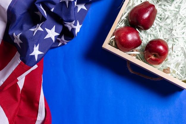 Bandera de estados unidos de américa y cajas de madera para fruta de manzana en azul