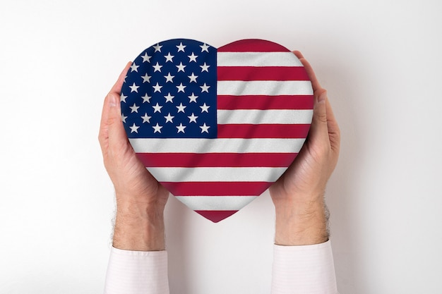 Bandera de estados unidos en una caja en forma de corazón en manos masculinas.