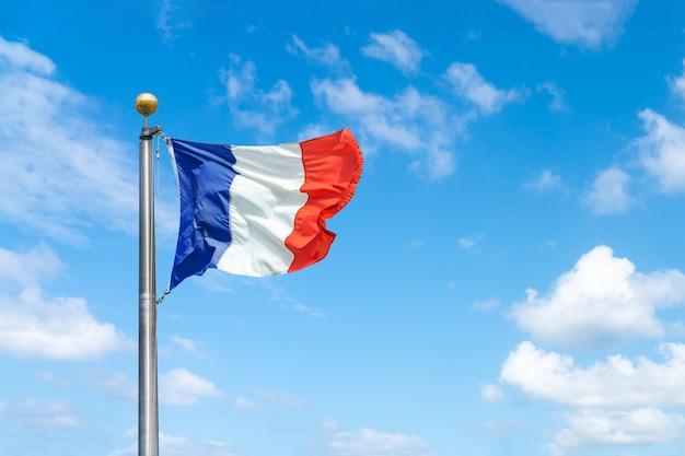 Una bandera francesa sobre un fondo de cielo azul