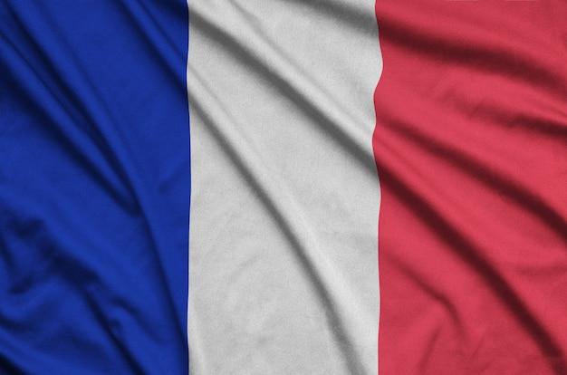 La bandera de francia está representada en una tela de tela deportiva con muchos pliegues.