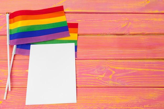 Bandera gay de arco iris brillante sobre fondo de madera y espacio en blanco