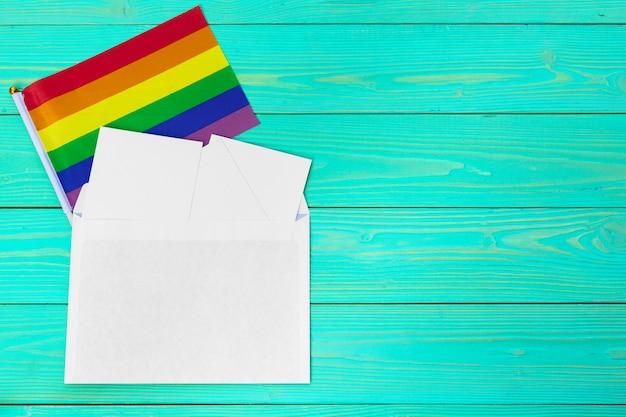 Bandera gay brillante arco iris en madera y espacio en blanco