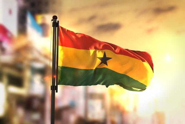 Bandera de ghana contra la ciudad borrosa de fondo a la salida del sol