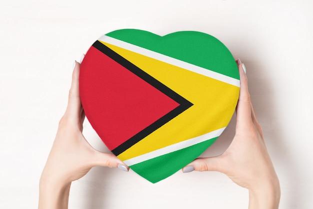 Bandera de guyana en una caja en forma de corazón en manos femeninas