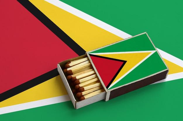La bandera de guyana se muestra en una caja de fósforos abierta, que está llena de fósforos y se encuentra en una bandera grande