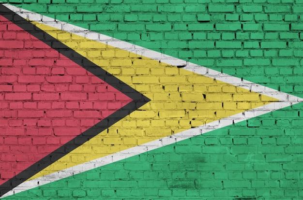 La bandera de guyana está pintada en una vieja pared de ladrillos