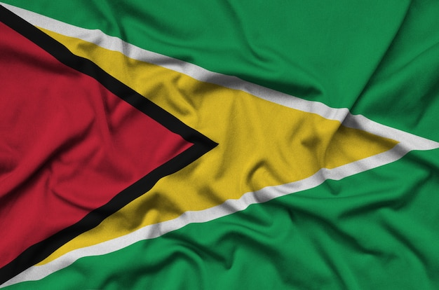 La bandera de guyana está representada en una tela de tela deportiva con muchos pliegues.