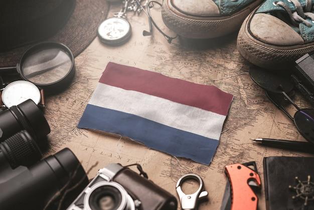 Bandera holandesa entre los accesorios del viajero en el viejo mapa vintage. concepto de destino turístico.