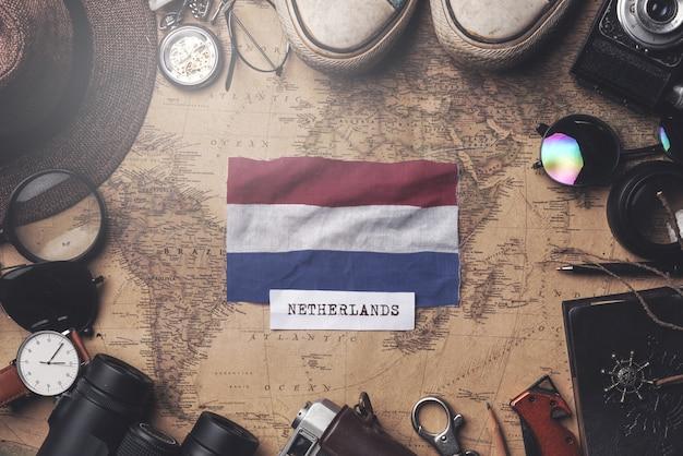 Bandera holandesa entre los accesorios del viajero en el viejo mapa vintage. tiro de arriba