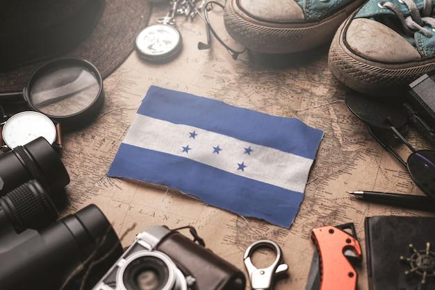 Bandera de honduras entre los accesorios del viajero en el viejo mapa vintage. concepto de destino turístico.