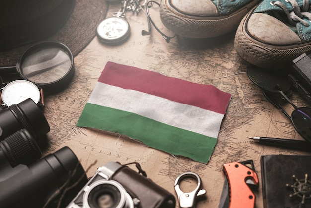 Bandera de hungría entre los accesorios del viajero en el viejo mapa vintage. concepto de destino turístico.