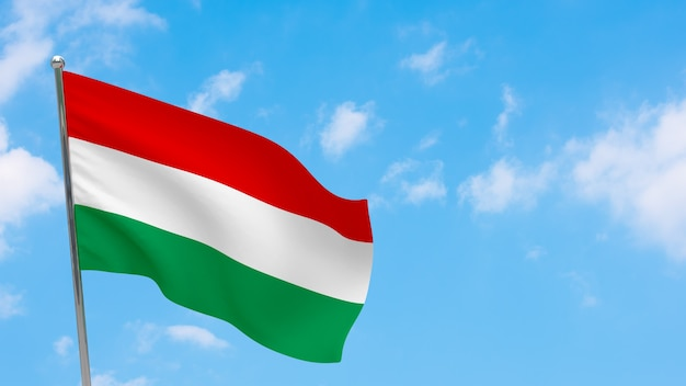 Bandera de hungría en la pole. cielo azul. bandera nacional de hungría