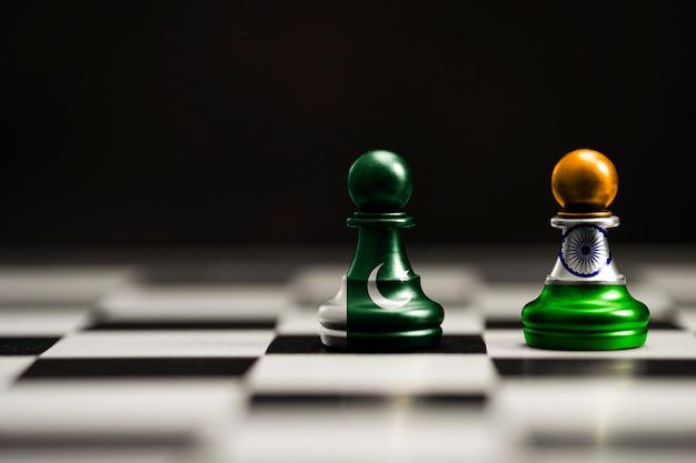 La bandera de india y pakistán imprime la pantalla en el ajedrez de la pata. ahora ambos países tienen aranceles económicos, guerra comercial y conflicto patriótico.