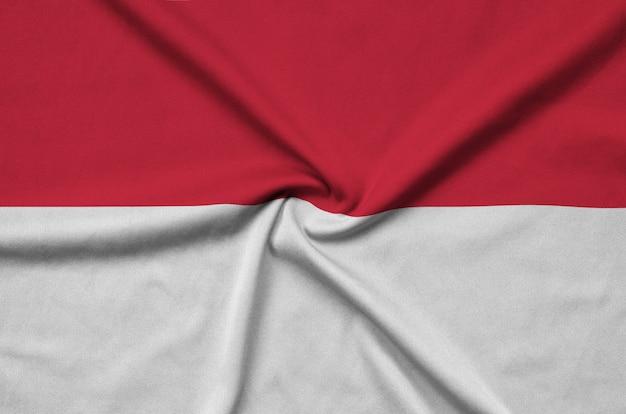 La bandera de indonesia está representada en una tela de tela deportiva con muchos pliegues.