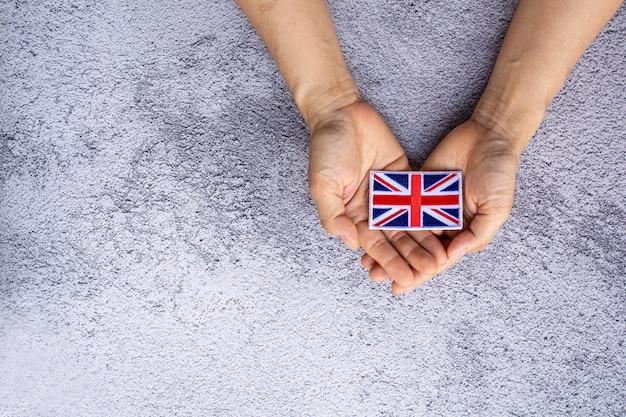 Bandera de inglaterra en una mano. concepto de amor, cuidado, protección y seguridad.