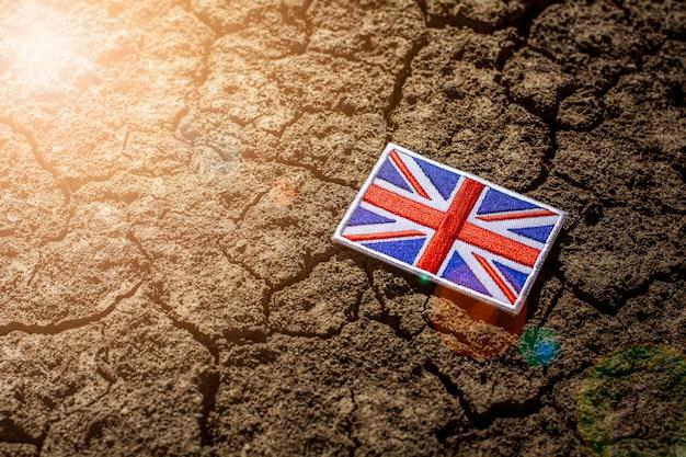 Bandera de inglaterra en tierra agrietada abandonada.