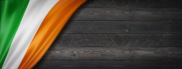 Bandera de irlanda en la pared de madera negra. banner panorámico horizontal.