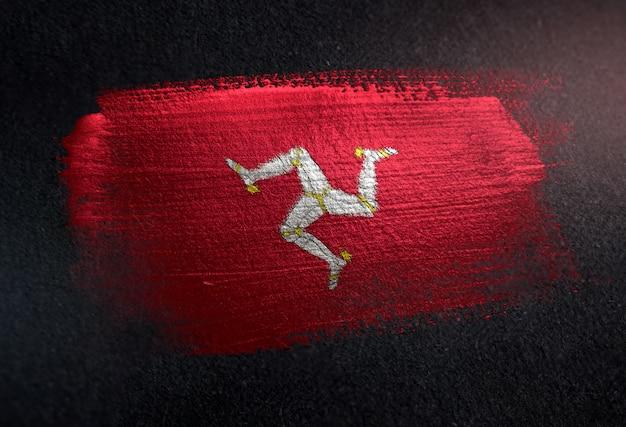 Bandera de la isla de man hecha de pintura de pincel metálico en la pared oscura de grunge