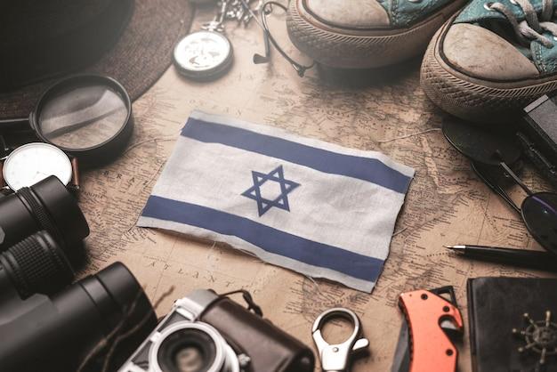 Bandera de israel entre los accesorios del viajero en el viejo mapa vintage. concepto de destino turístico.
