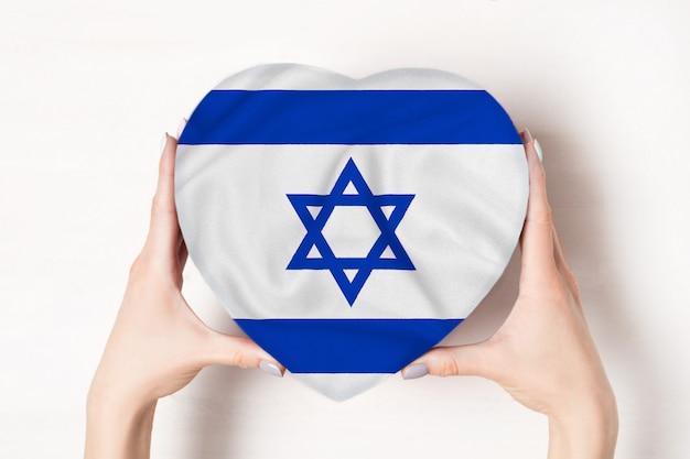 Bandera de israel en una caja en forma de corazón en manos femeninas.