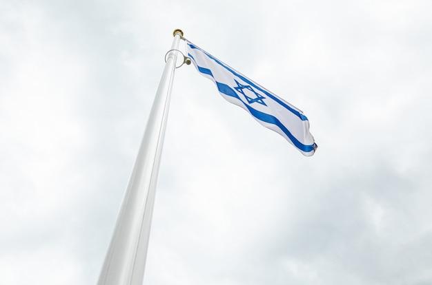 Bandera de israel en un flagstuff delante del cielo
