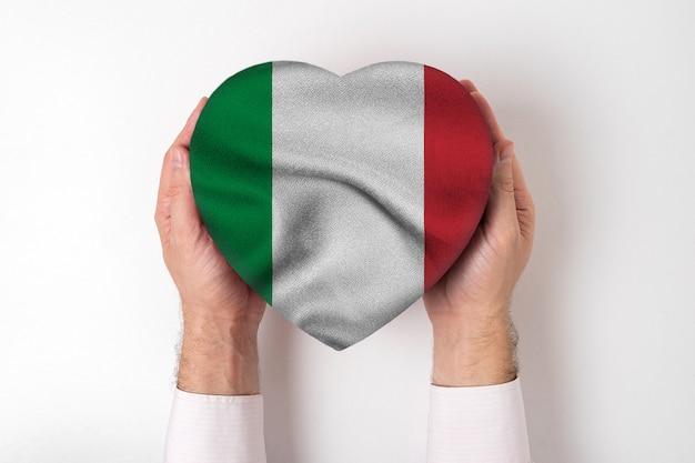 Bandera de italia en una caja en forma de corazón en manos masculinas.