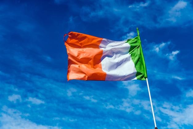 Bandera de italia ondeando contra el cielo azul con nubes.