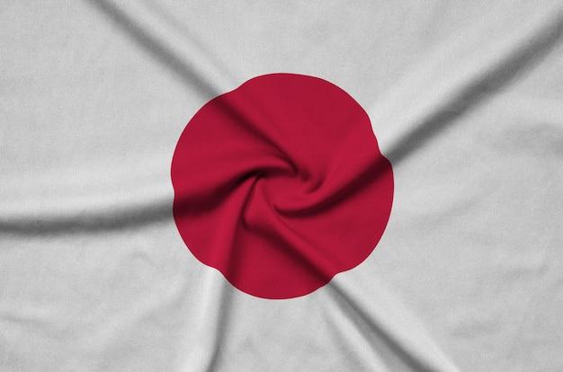 La bandera de japón está representada en una tela de tela deportiva con muchos pliegues.