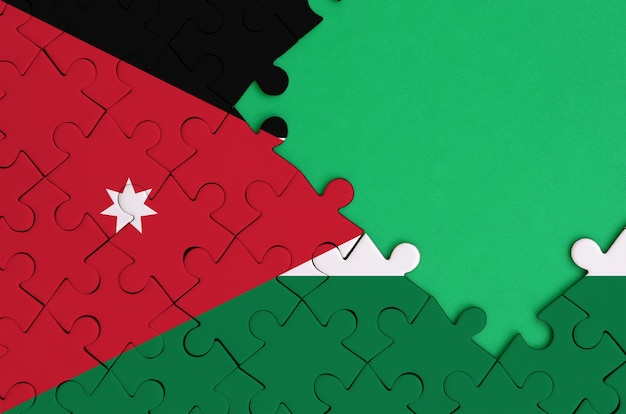 La bandera de jordan está representada en un rompecabezas completo con espacio de copia verde gratis en el lado derecho