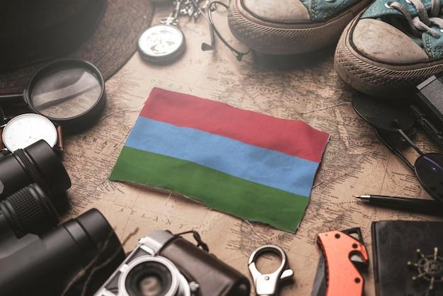 Bandera de karelia entre los accesorios del viajero en el viejo mapa vintage. concepto de destino turístico.