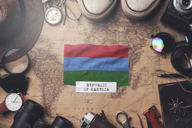 Bandera de karelia entre los accesorios del viajero en el viejo mapa vintage. tiro de arriba