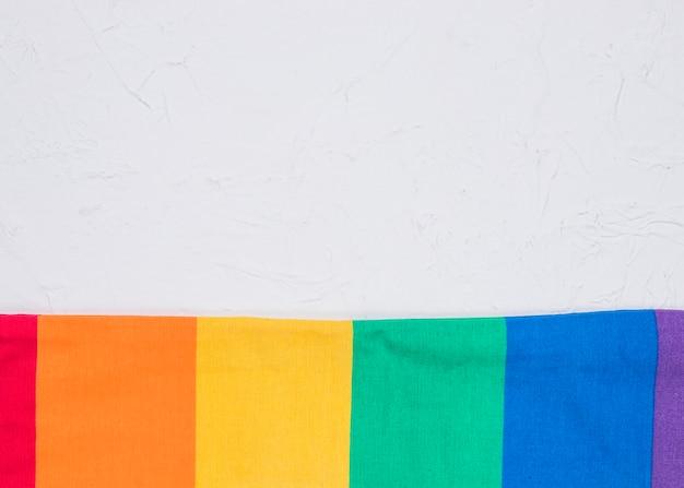 Bandera lgbt alisada sobre superficie blanca.