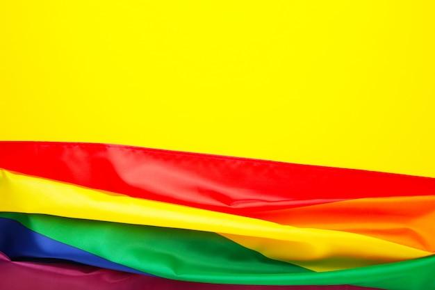Bandera lgbt del arco iris sobre fondo amarillo con espacio de copia