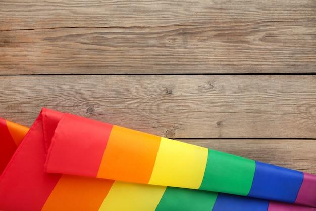 Bandera lgbt del arco iris sobre fondo de madera gris con espacio de copia