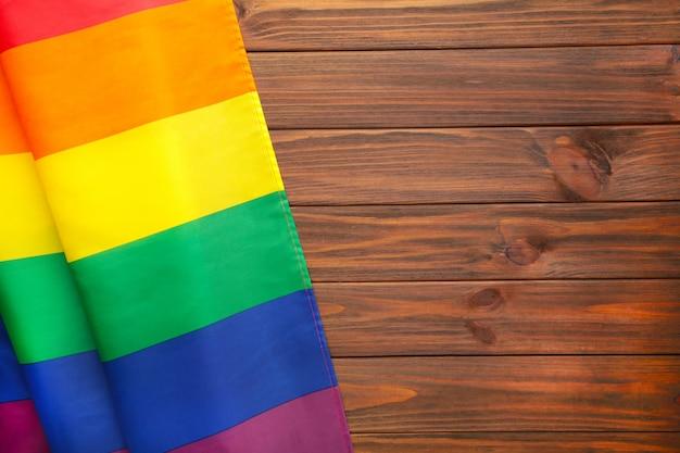 Bandera lgbt del arco iris sobre fondo de madera marrón con espacio de copia