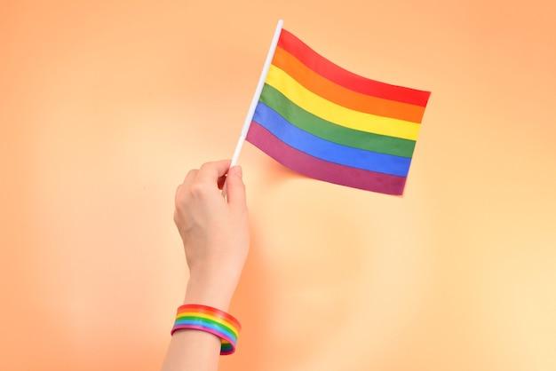 Bandera lgbt en mano de mujer sobre fondo naranja. copie el espacio.