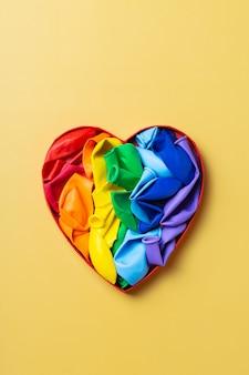 Bandera lgbtq del arco iris en forma de corazón contra el mes del orgullo de fondo amarillo