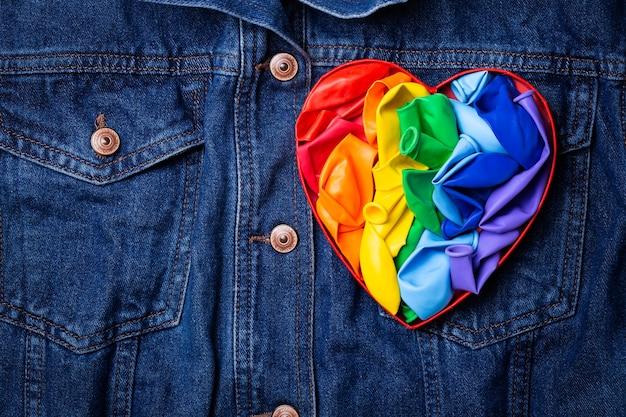 Bandera lgbtq del arco iris en forma de corazón contra el mes del orgullo de fondo de mezclilla