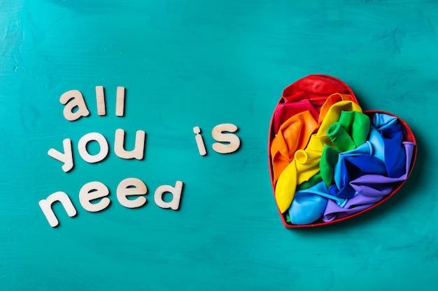 Bandera lgbtq del arco iris en forma de corazón contra el mes del orgullo de fondo turquesa