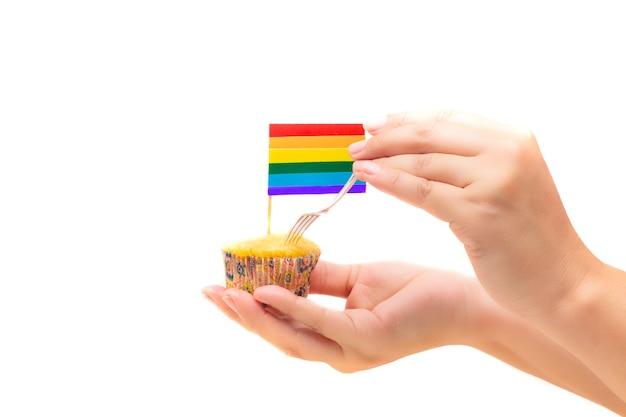 Bandera lgtb en un cupcake sostenido por una mano aislada sobre fondo blanco.