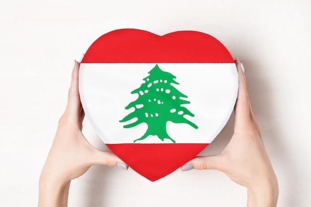 Bandera del líbano en una caja en forma de corazón en manos femeninas