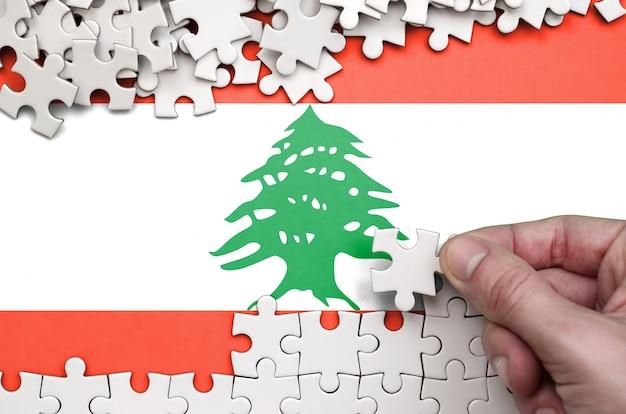 La bandera del líbano está representada en una mesa en la que la mano humana dobla un rompecabezas de color blanco.