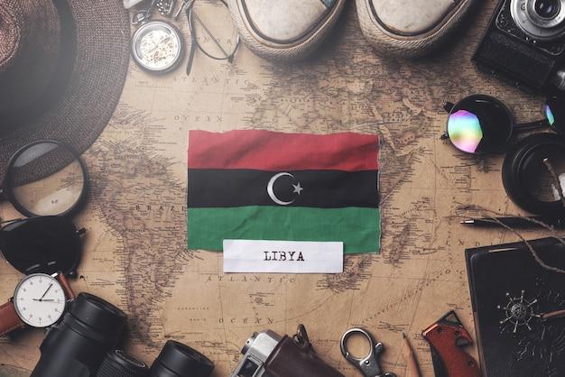 Bandera de libia entre los accesorios del viajero en el viejo mapa vintage. tiro de arriba