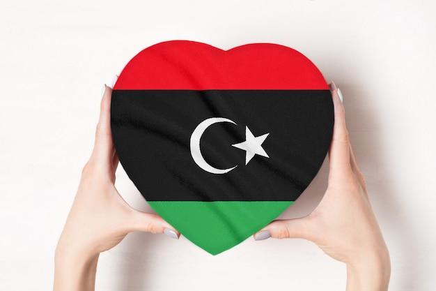 Bandera de libia en una caja en forma de corazón en manos femeninas.