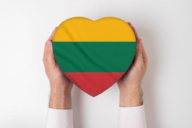 Bandera de lituania en una caja en forma de corazón en manos masculinas.