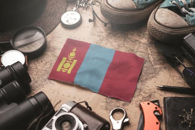 Bandera de mongolia entre los accesorios del viajero en el viejo mapa vintage. concepto de destino turístico.