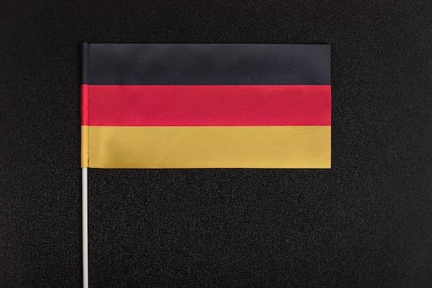 La bandera nacional de alemania sobre fondo negro. símbolos nacionales de alemania