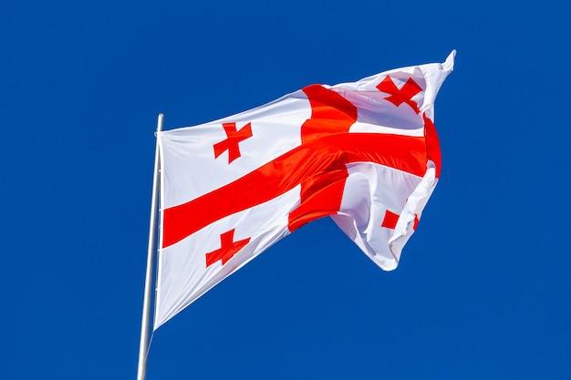 La bandera nacional de georgia ondeando en el viento sobre un cielo azul