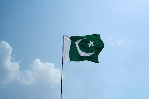 La bandera nacional de pakistán volando en el cielo azul con nubes