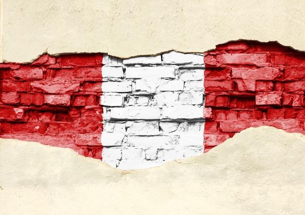 Bandera nacional del perú sobre un fondo de ladrillo. pared de ladrillo con yeso, fondo o textura parcialmente destruidos.